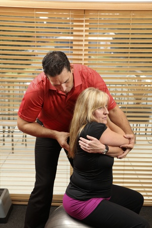 Chiropractor adjusting a patiant sitting on a ball photo