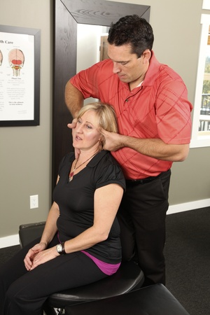 adjustment: Chiropractor adjusting a female patient Stock Photo