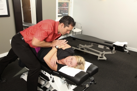 spinal adjustment: Chiropractor adjusting a female patient Stock Photo