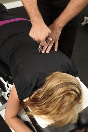 Chiropractor adjusting a female patient photo
