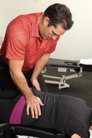 Chiropractor adjusting a female patient Reklamní fotografie