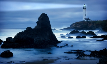 Lighthouse at the California coast with light beam