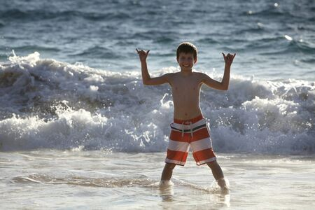 hang loose: cute young boy standing in the ocean showing the hang loose sign Stock Photo
