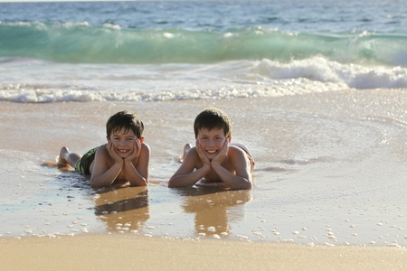 two cute boys laying at the beach photo