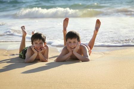 2 つのかわいい男の子を浜の敷設 写真素材