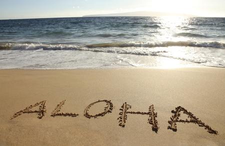 the word Aloha written in a sandy beach Imagens