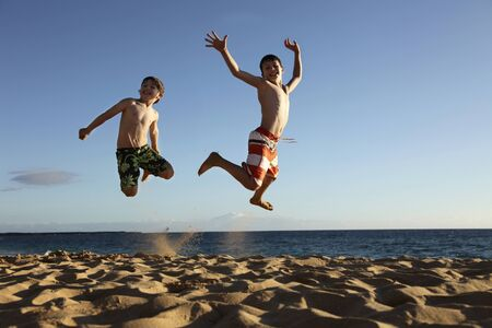 two boys jumping at the beach photo