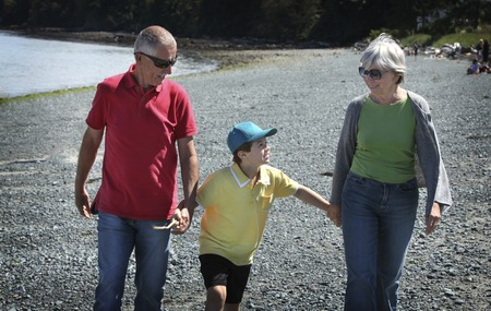 Grandparents with grandson walking at the beach photo
