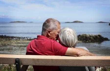 pareja besandose: Feliz pareja de ancianos bes�ndose en un banco Foto de archivo