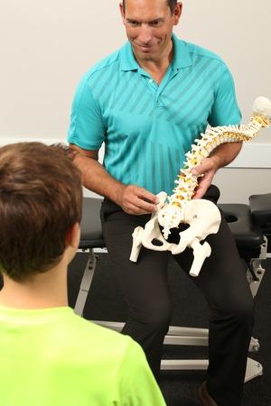 Een Chiropractor toont een model van de menselijke wervelkolom een kind
