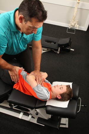 A Chiropractor treating a child photo