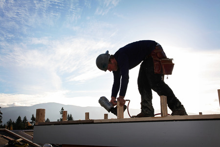 helmet construction: A carpenter working on a consruction site Stock Photo
