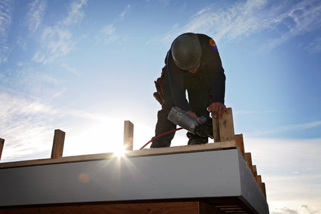 roof structure: A carpenter working on a consruction site Stock Photo