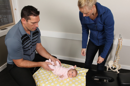 A chiropractor treating a new born baby Stock Photo