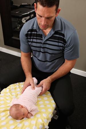 Een chiropractor de behandeling van een pasgeboren baby