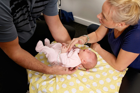 A chiropractor treating a new born baby Stockfoto