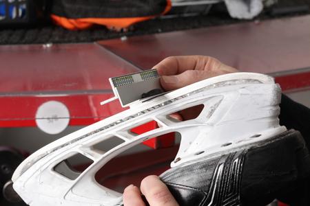 patinar: Control final de la hoja afilada de un patín del hockey Foto de archivo