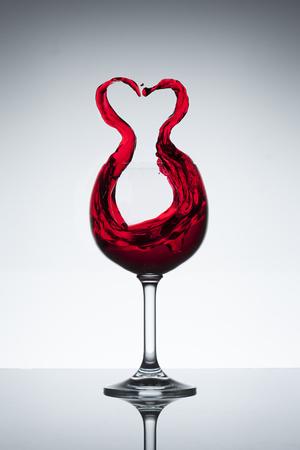 Rode wijn spatten uit een glas in hartvorm Stockfoto