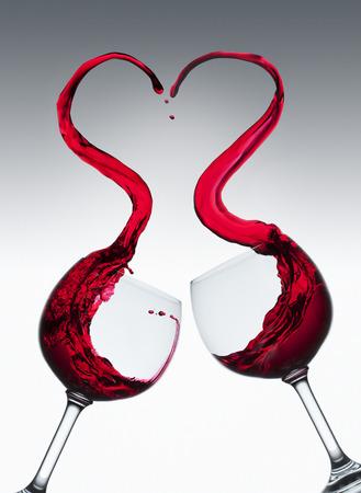 Rode wijn spatten van twee glazen in hartvorm