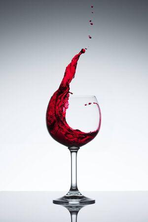 Rode wijn uit een glas water.  Stockfoto