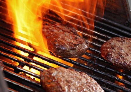 Burger pattie op een barbecue met vlammen Stockfoto