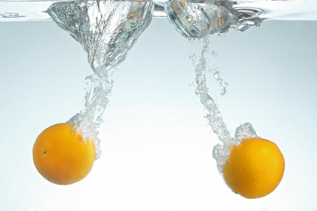 Twee Sinaasappelen laten vallen in water met plons