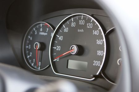 rev: A closeup of a car dashboard with a speedometer in focus and a tachometer slightly out of depth of field