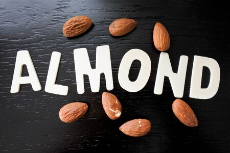 Almond, Close up word arrangement from wood pieces alphabet and toasted almond on black background. Stok Fotoğraf