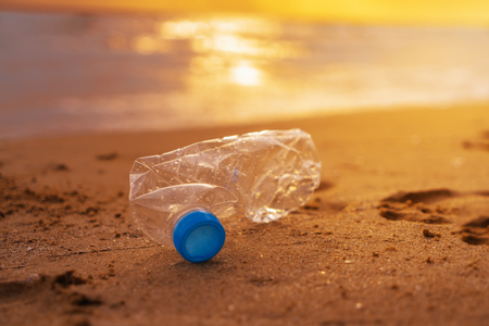 The plastic bottle  on the beach at the sunset
