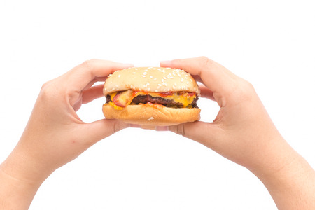 Female hand holding burger in isolate background.