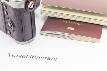 itinerary: Passport and camera on travel itinerary paper : can use this for tourism concept. Stock Photo