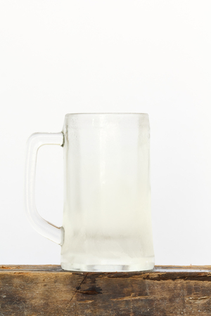 Cool empty glass beer on wood with white background.