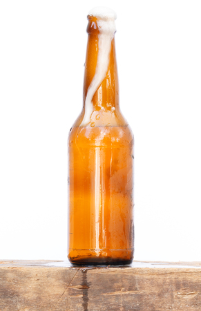international beer: International beer day with foam of beer flow over cool bottle on the wood. Stock Photo