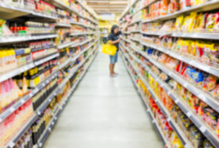 Blurred supermarket and woman shopping product.