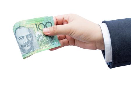 australian dollars: Businessman hand holding roll Australian dollars (AUD) on isolated background.