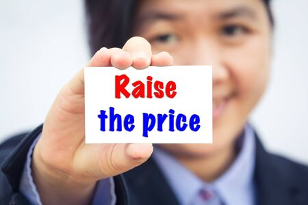 raise: Businesswoman holding card with Raise  the price message.
