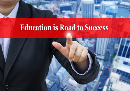 blurr: Businessman pointing to Education is Road to Success on blurr business building background. Stock Photo