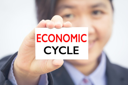 economic cycle: Businesswoman holding card with ECONOMIC CYCLE message. Stock Photo