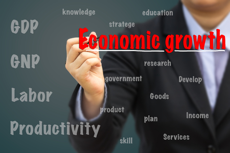 Businessman writing Economic growth relation concept.