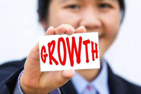 businesswoman card: Businesswoman holding card with GROWTH message. Stock Photo