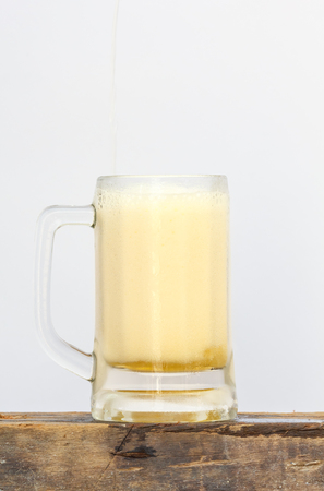international beer: International beer day with pouring beer into mug on wood and white background. Stock Photo