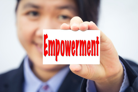 empowerment: Businesswoman holding card with Empowerment message. Stock Photo