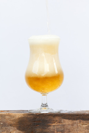 international beer: International beer day with pouring beer into glass on wood and white background. Stock Photo