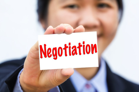 negotiation: Businesswoman holding card with negotiation message.