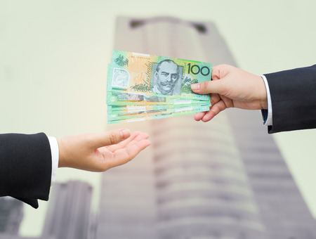 money bills: Hands of businessman passing Australian dollar (AUD) banknote with blurred office building background. Stock Photo