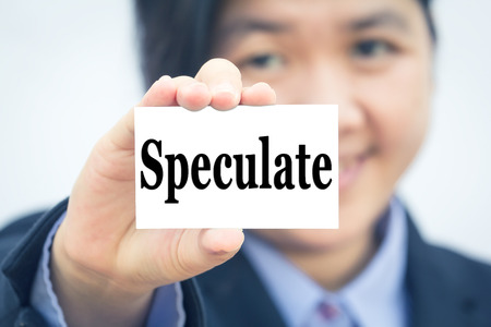 speculate: Businesswoman holding card with Speculate message. Stock Photo