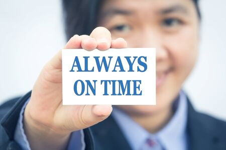 always: Businesswoman holding card with ALWAYS ON TIME message. Stock Photo