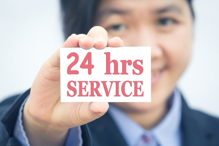 hrs: Businesswoman holding card with 24 hrs SERVICE message.