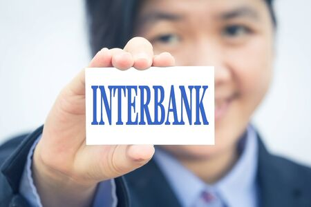 interbank: Businesswoman holding card with INTERBANK message. Stock Photo