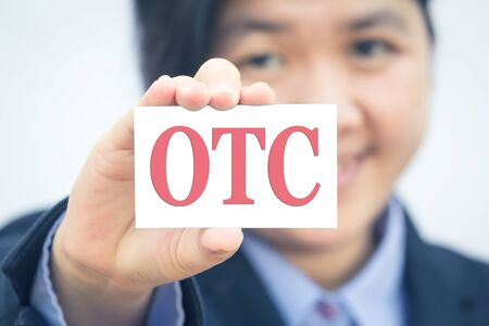 Businesswoman holding card with OTC message. 版權商用圖片